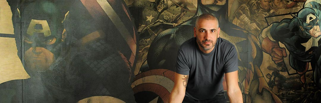 Axel Alonso - Infront of wall art of Captain America marvel comic character