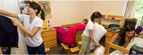 New students arrange their dorm room with the help of a parent